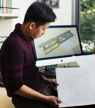 Image of Viet Trinh looking at an embossed map. In the background , a computer display shows a 3-D map of a building, built using SIM.